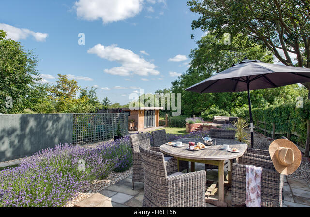 A British Garden On A Sunny Summers Day. Patio Furniture, Table Set Ready  For