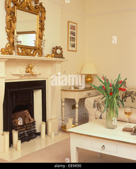 Ornate Gilt Mirror Above Fireplace In Cream Living Room With Table