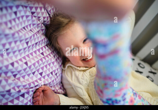 Girl laughing while playing on day bed - Stock Image