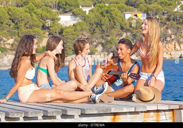 Sporty teen boy in bathing trunks lying on side tanning himself on  Hawaiian beach in Maui Getty Images