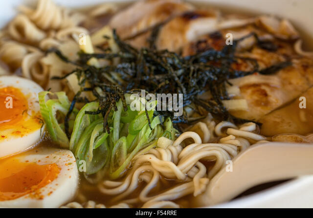 Plate Of Chinese Soup With Chicken Egg Noodles Greens And Seaweeds On White