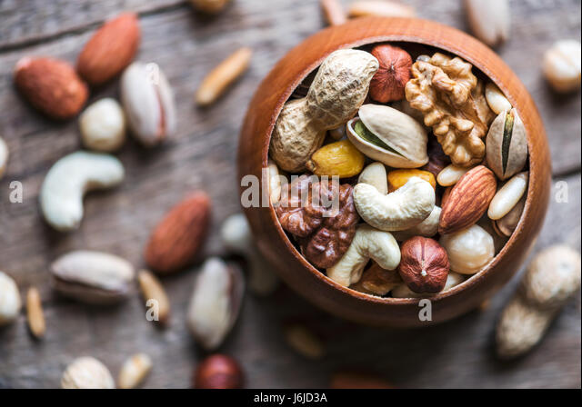 Dried mixed nuts in wooden bowl closeup. Walnut, pistachio, hazelnut, almond and other. Studio macro shoot. - Stock Image