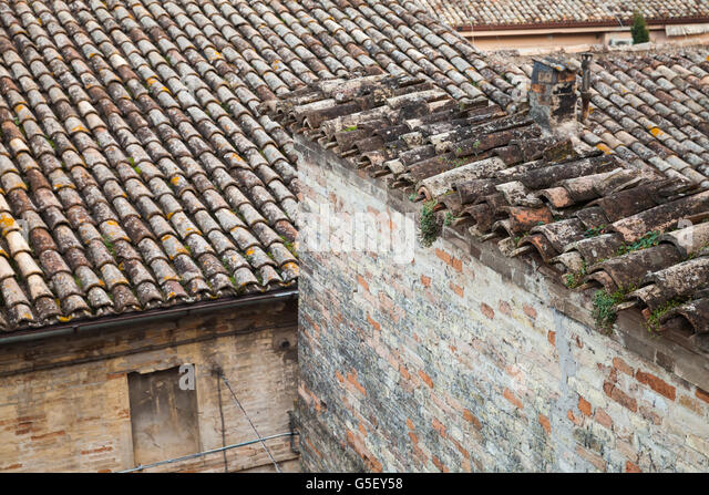 Old roofs in Fermo, Italy. Stone living houses exterior - Stock Image