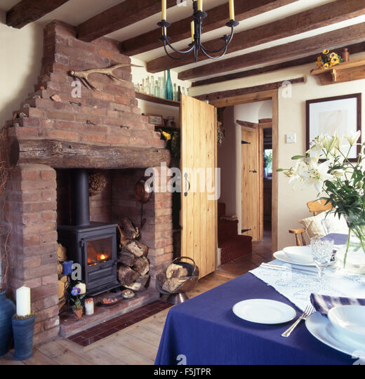 Wood Burning Stove In Exposed Brick Fireplace In A Cottage Dining Room With  A Blue Cloth