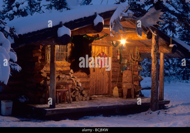 Interior Alaska Log Cabin Forest Winter Porch Light Snow Sky Dusk   Stock  Image