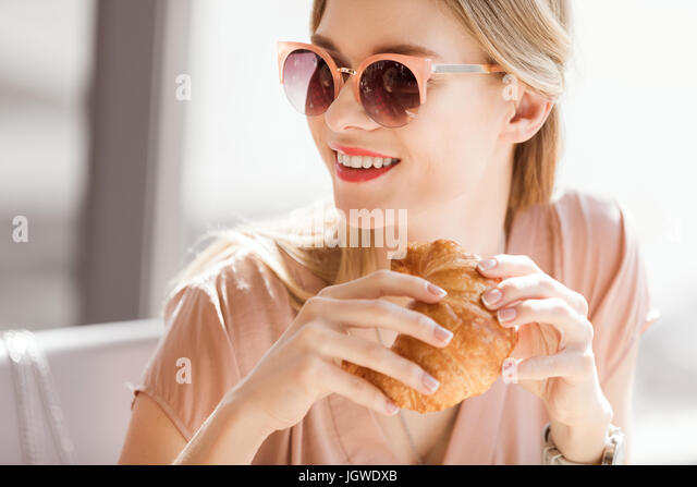 young woman eating croissant while sitting in cafe, coffee break - Stock Image