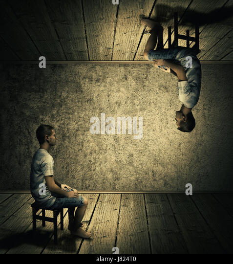 Creative idea concept with a man sitting in a dark room above and below looking at each others twin. Conceptual - Stock Image