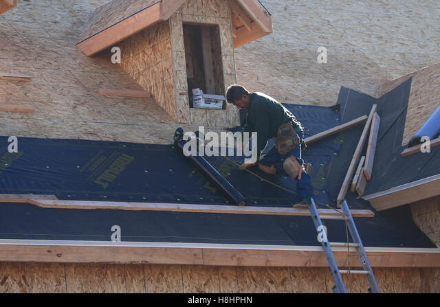 Man Roofer Laying Down Tar Paper On A New Roof   Stock Image