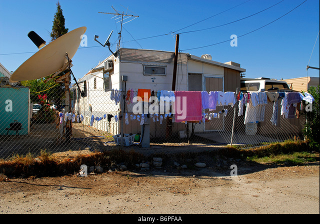 Trailer Park With Large Satellite Dish Drying Laundry On Chainlink Fence Desert Shores