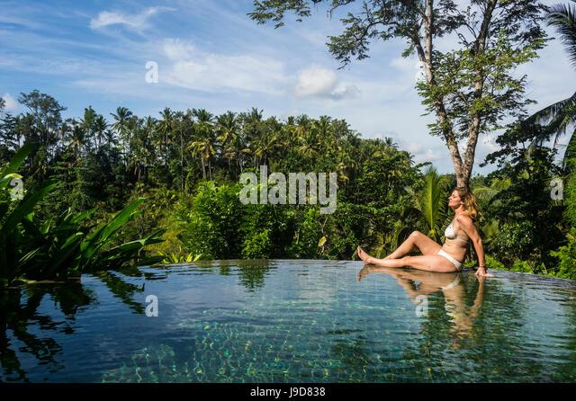 Woman enjoying an overflowing pool above a valley in the Kamandalu Ubud resort, Ubud, Bali, Indonesia, Southeast - Stock Image