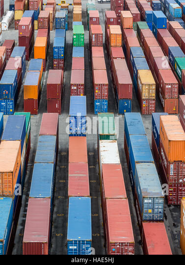Many colorful shipping containers at a coastal freight yard - Stock Image