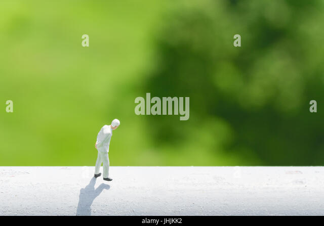 Business and financial  concept. Miniature people : businessman thinking or making decision by walking on high white - Stock Image