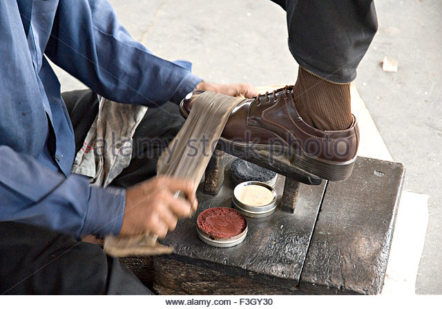 Person doing shoe polish at Kandivali Railway station ; Bombay Mumbai ;  Maharashtra ; India -