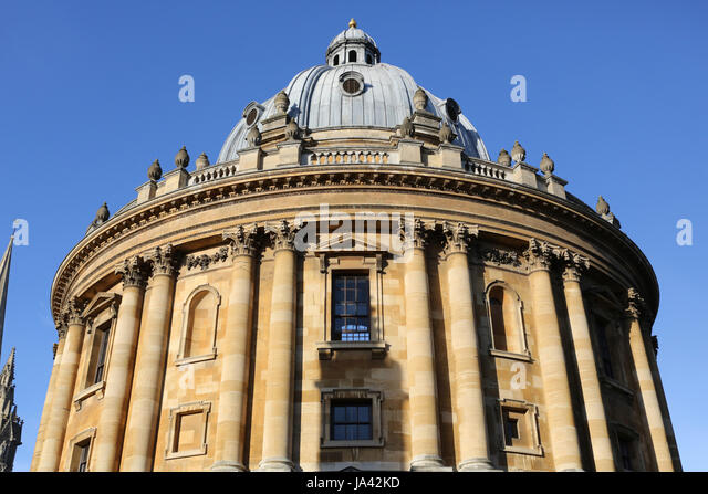 Top half of the Oxford Radcliffe Camera building in early morning sunlight and blue sky - Stock Image