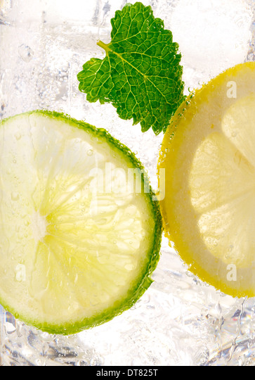 ... detail of a lemon lime soda with a mint leaf with ice in a clear glass