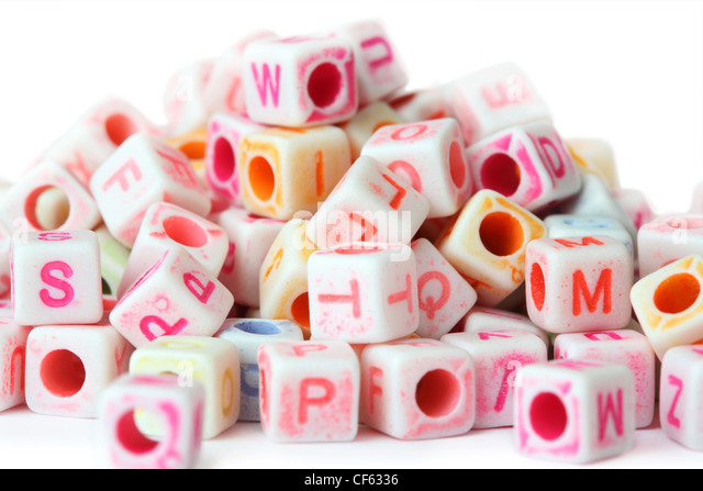 many little cube beads with letters isolated on white stock image