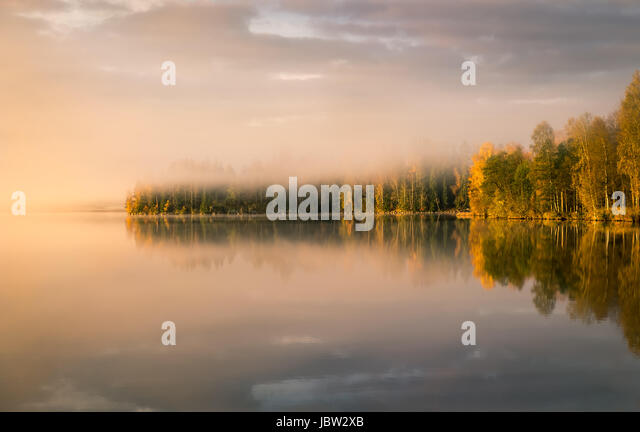 Scenic landscape with lake and fall colors at morning light - Stock Image