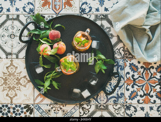 Summer refreshing cold peach ice tea in jars on tray - Stock Image