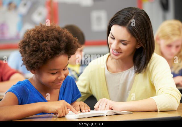 Teacher Reading With Female Pupil In Class - Stock Image