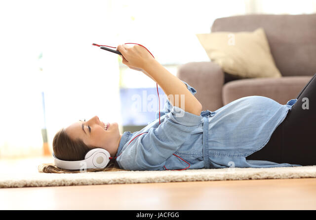 Side view of a pregnant woman listening music with headphones and a smart phone lying on the floor at home - Stock Image