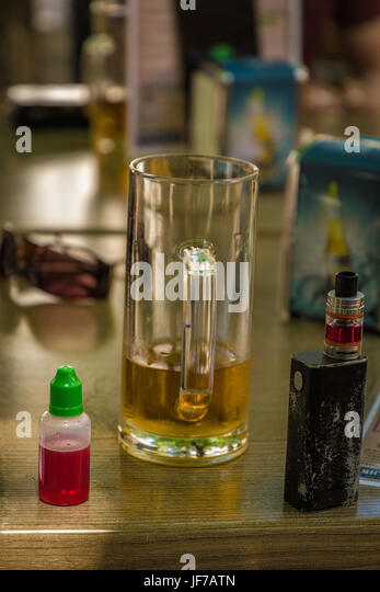Vaporizer and almost empty beer with bottle and fork on table - Stock Image