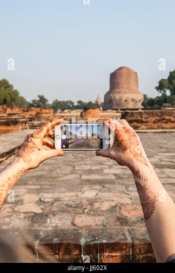 A woman taking a picture of Dhamekh Stupa in Sarnath, India with her iPhone. - Stock Image