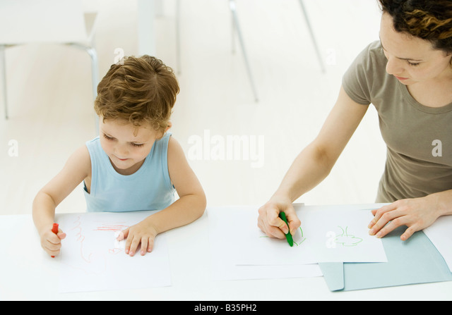 Mother And Son Sitting Side By Coloring With Crayons