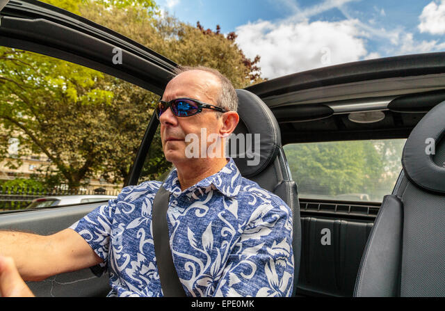 A Middle Aged Man Driving A Cabriolet Car With The Roof Down On A Summer Day