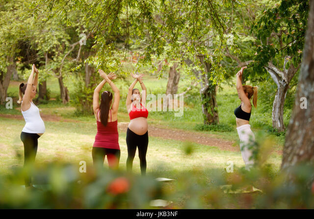 Pregnant women, group of moms training with coach doing fitness exercises and yoga during pregnancy in park. - Stock Image