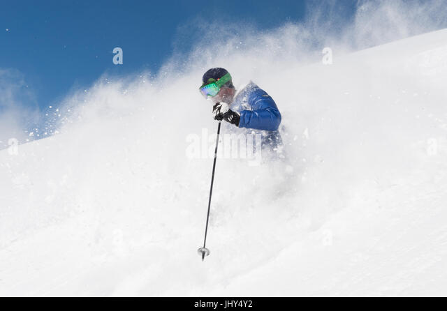Skier going through fresh powder in the ski region of Disenits,Switzerland - Stock Image