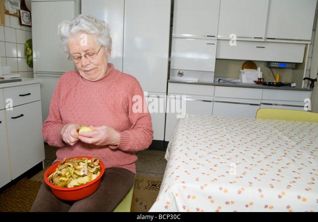 frau in ihren siebzigern sitzt in der kche und schlt kartoffeln stock image - Rote Kche