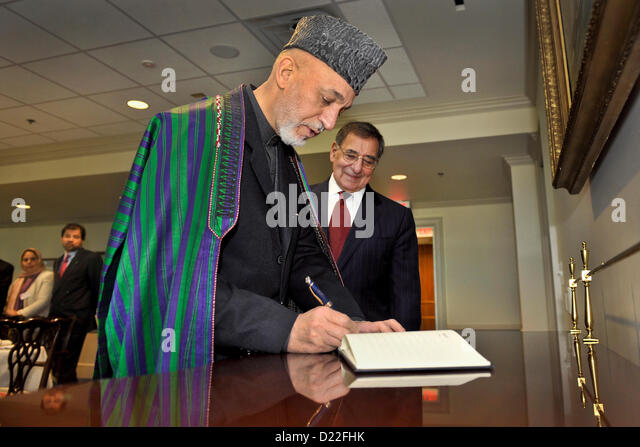 afghan president hamid karzai signs a guest book as secretary of defense leon panetta looks on