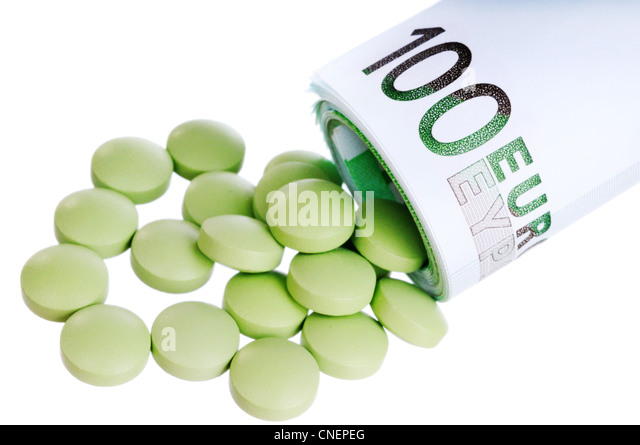 Green round pills fall out a sheaf of 100 euro papers - Stock Image