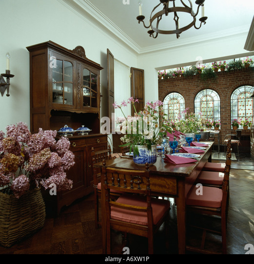 Formal Diningroom With Dark Wood Dresser And Pink Cushions On Chairs