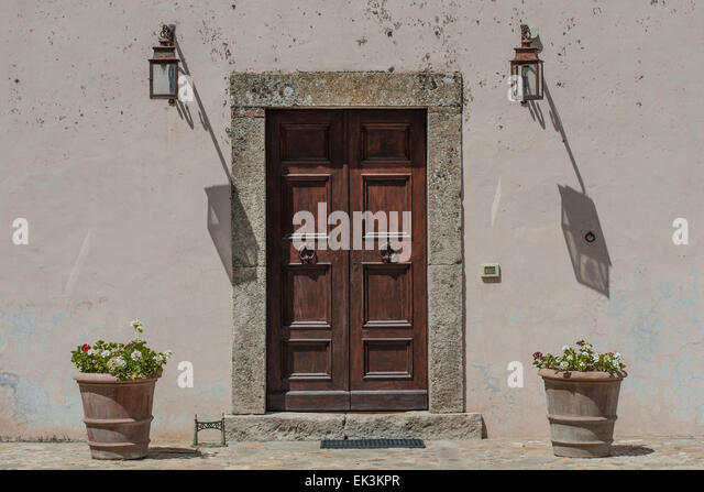 A Big Heavy Front Door On An Italian House With The Shadow Of Lights And Pot