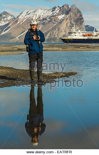 a photographer stands on a beach near a cruise ship stock image - Cruise Ship Photographer