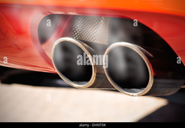 Close Up Of A Red Car Dual Exhaust Pipe With Smoke Around It   Stock Image