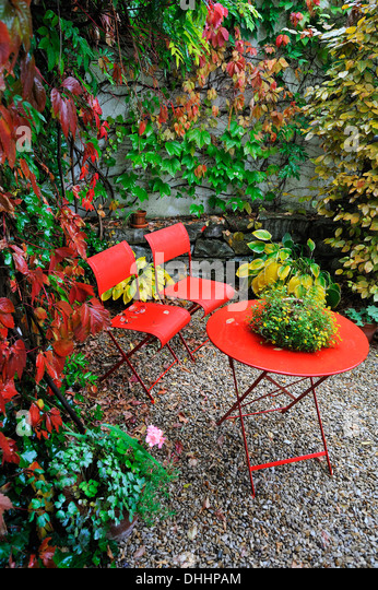 red garden chairs and table in the rain in an autumn garden corner middle franconia