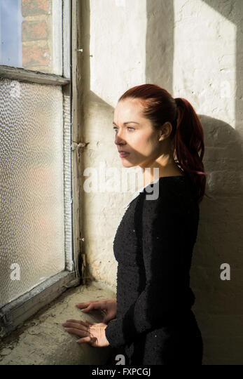 redhead woman looking out of the window stock image