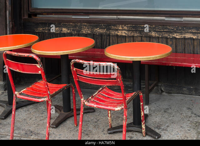 Worn Red Chairs And Tables In Front Of A French Style Cafe In New York City