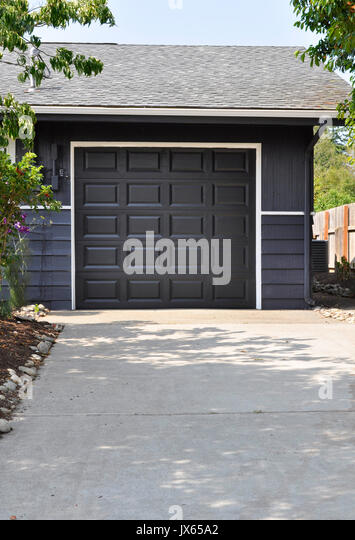 exterior single car garage with the door closed in a dark gray or charcoal color at