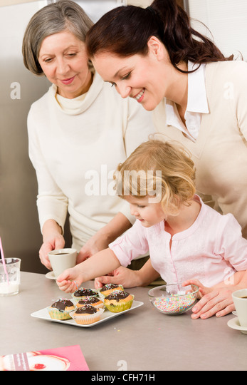 mother and daughter decorating cupcakes sprinkles happy together at home stock image - Woman Decorating Cupcakes