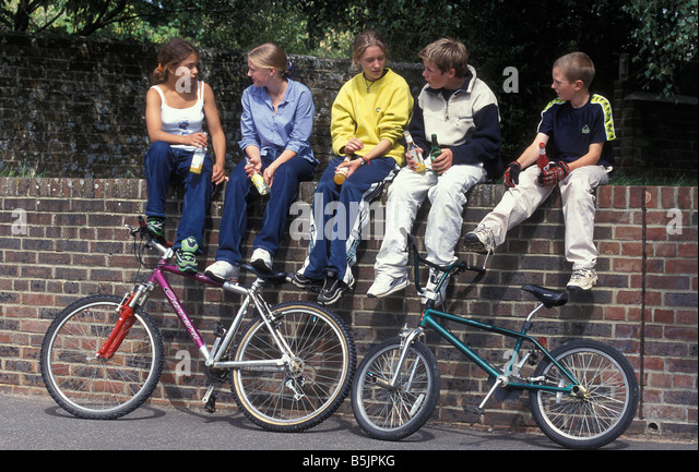 boys-and-girls-with-bikes-sitting-on-wal