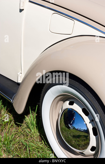 classic car with steel rims with chrome center caps and whitewall tires stock image