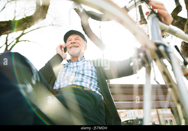 Senior man with bicycle and smart phone, making phone call - Stock Image
