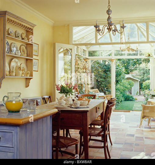 Old Pine Table And Chairs In Country Kitchen With Doors Open To Conservatory Extension View