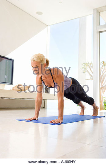 Mature Woman Doing Push Ups On Exercise Mat In Living Room