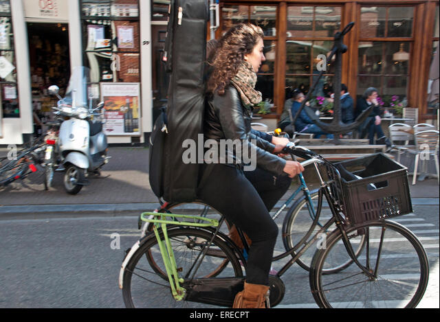Woman Carrying Instrument On Her Back A Bicycle