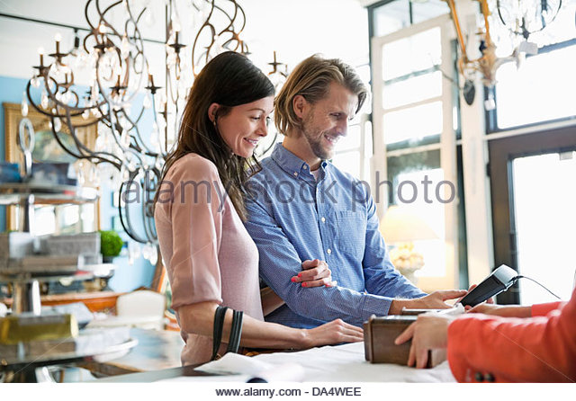 Couple paying for purchase at furniture store   Stock Image. Furniture Shop Sale Stock Photos   Furniture Shop Sale Stock