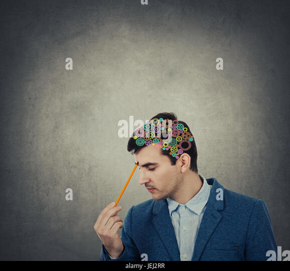 Creativity concept of a businessman pointing with a pencil to his head with a colorulful brain made from gears over - Stock Image